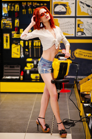 Red haired model posed with big drill or demolition hammer at store or household shop of working tools.