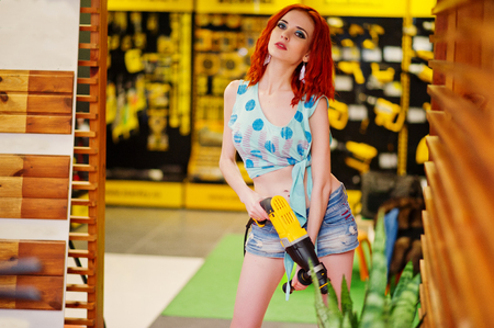 Red haired model posed with drill at store or household shop of working tools. Stock Photo