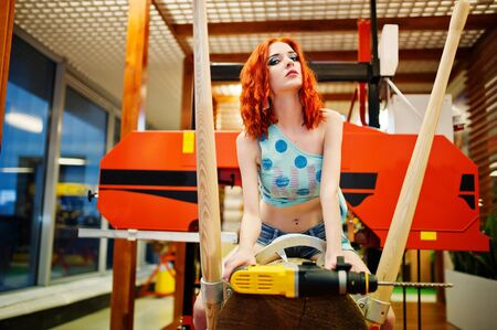 Red haired model sitting on wood sawmill with drill at store or household shop of working tools. Stock Photo