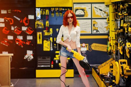 pastime: Red haired model posed with large angle grinder at store or household shop of working tools. Stock Photo
