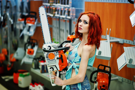 Red haired slim model posed with chainsaw at hands on store or household shop of working tools.