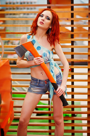 Red haired slim model posed with axe at store or household shop of working tools. Stock Photo