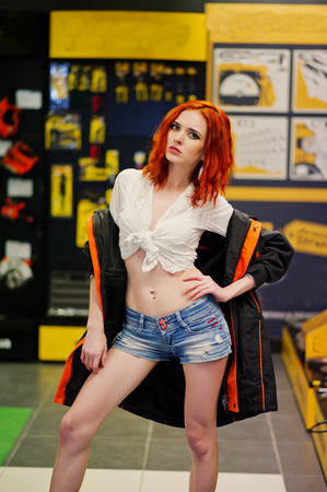 Red haired model posed weared on working jacket at store or household shop of working tools. Stock Photo