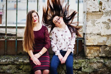 Two young teenages girl sitting against iron fence and moving with they hair. Plump girl vs thin. Friends teen. Stock Photo