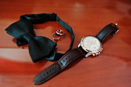 Mens accessories for groom at wedding: watches, bow tie and rings.