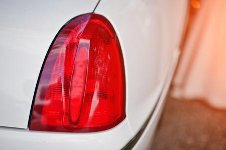 brightness: Red back headlight of white luxury limousine car. Stock Photo