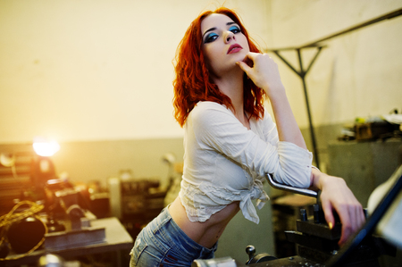 Red haired girl wear on short denim shorts and white blouse posed at industrial machine at the factory.