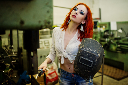Red haired girl wear on short denim shorts and white blouse with welding mask at hands posed at industrial machine at the factory.