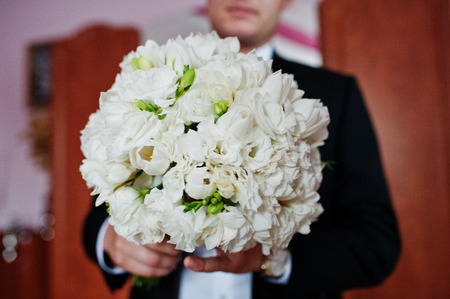 Stylish groom with wedding bouquet at hands on his room. Stock Photo