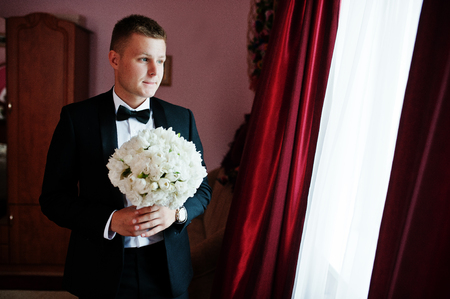 cuff: Stylish groom with wedding bouquet at hands on his room. Stock Photo