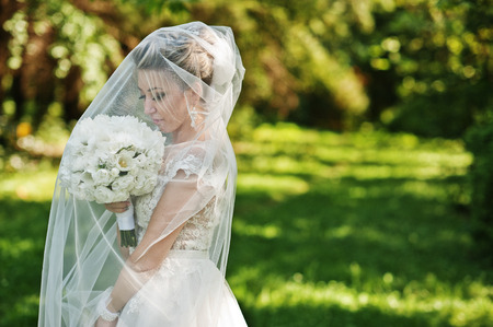 Awesome gorgeous blonde bride under veil with wedding bouquet at hands.