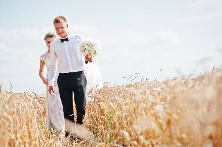 village man: Wedding couple at field of wheat in love.