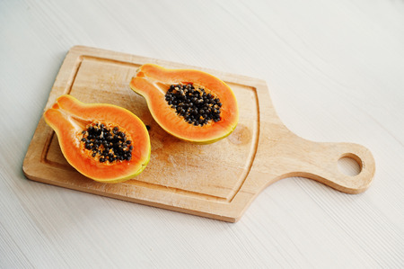 Exotic fruit papaya or papaw isolated on white background on wooden board. Healthy eating dieting food.