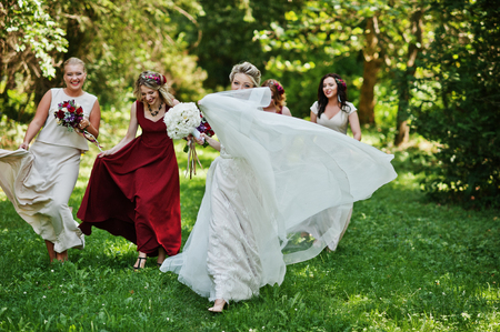 Gorgeous blonde bride with four bridesmaids at red and beige dresses outdoor.