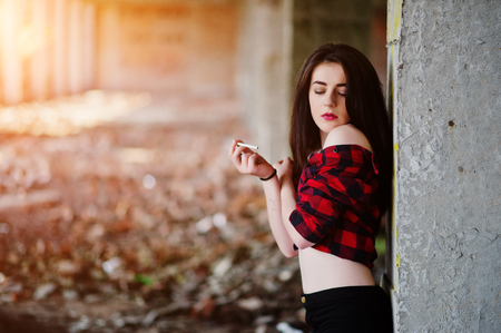 Portrait smoking girl with red lips wearing a red checkered shirt with bare shoulders posed sexy background abadoned place.