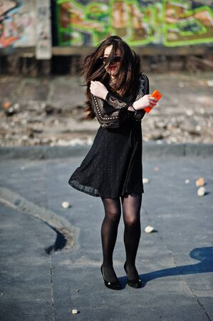 Portrait brunette girl with red lips and orange mobile phone at hands, wearing a black dress, sunglasses posed on the roof. Street fashion model.