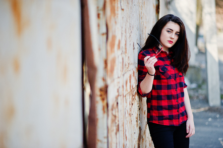 Fashion portrait girl with red lips wearing a red checkered shirt and sunglasses background rusty fence.