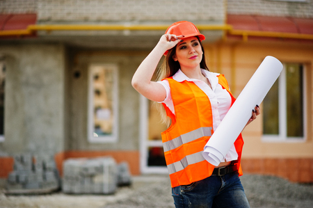 Engineer builder woman in uniform waistcoat and orange protective helmet hold business paper against new building. Property living block theme.