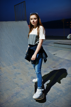holiday spending: Young teenage urban girl with skateboard, wear on glasses, cap and ripped jeans at skate park on the evening. Stock Photo