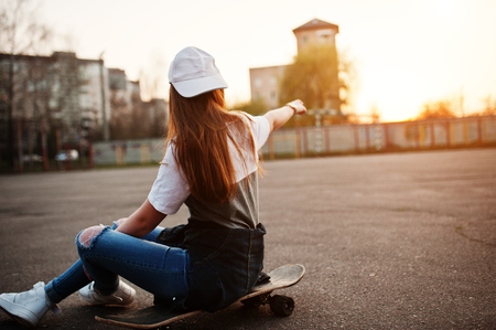 Young teenage urban girl with skateboard, wear on glasses, cap and ripped jeans at the yard sports ground on sunset showed finger on sky. Reklamní fotografie
