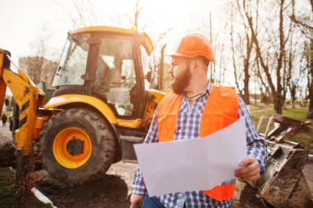 Brutal beard worker man suit construction worker in safety orange helmet against traktor with plan paper at hands.
