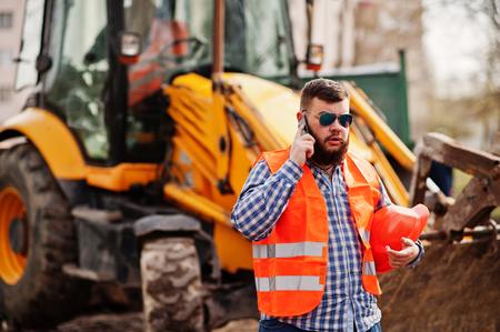 trustworthy: Brutal beard worker man suit construction worker in safety orange helmet, sunglasses against traktor with mobile phone at hand.