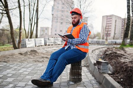 Brutal beard worker man suit construction worker in safety orange helmet sitting on pavement and makes working notebook entries. Stock Photo