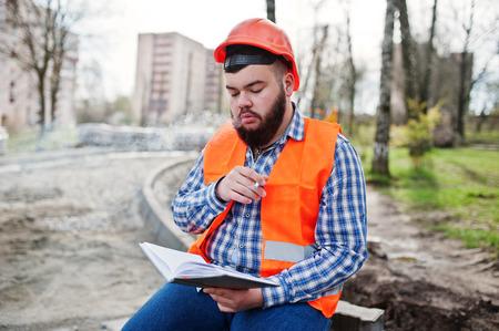 Brutal beard smoking worker man suit construction worker in safety orange helmet sitting on pavement, break at work, and read working notebook entries.