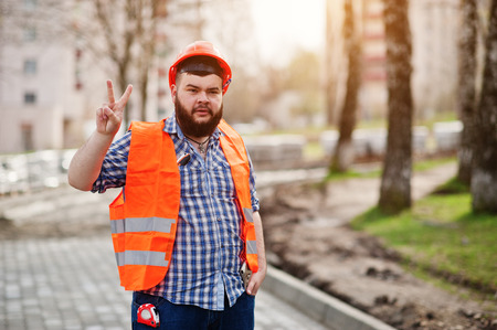 trustworthy: Portrait of brutal beard worker man suit construction worker in safety orange helmet against pavement with shows two finger. Stock Photo