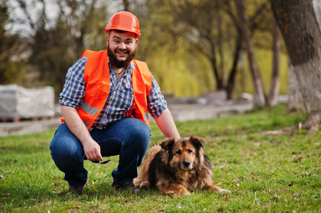 trustworthy: Portrait of brutal beard worker man suit construction worker in safety orange helmet with watchdog.