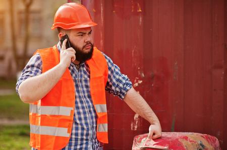 trustworthy: Brutal beard worker man suit construction worker in safety orange helmet near red barrel speak on phone.
