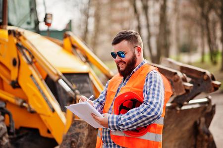 Brutal beard worker man suit construction worker in safety orange helmet, sunglasses against traktor with plan paper at hands. Foto de archivo