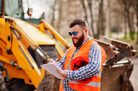 Brutal beard worker man suit construction worker in safety orange helmet, sunglasses against traktor with plan paper at hands. Standard-Bild