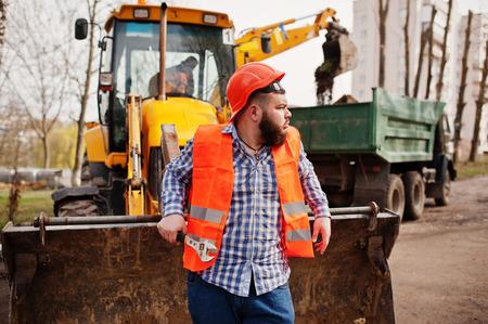 trustworthy: Brutal beard worker man suit construction worker in safety orange helmet, against traktor with adjustable wrench at hand.