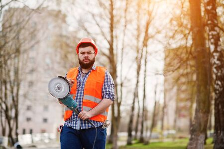 Portrait of brutal beard worker man suit construction worker in safety orange helmet against pavement with angular grinding machine in hand.