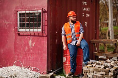 trustworthy: Brutal beard worker man suit construction worker in safety orange helmet sitting on red barrel. Stock Photo