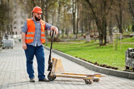 Brutal beard worker man suit construction worker in safety orange helmet with pallet truck.
