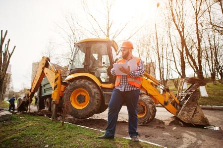 trustworthy: Brutal beard worker man suit construction worker in safety orange helmet, sunglasses against traktor with plan paper at hands. Stock Photo