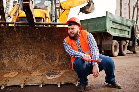trustworthy: Brutal beard worker man suit construction worker in safety orange helmet, against traktor with hammer at hand.