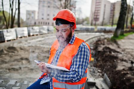 trustworthy: Brutal beard smoking worker man suit construction worker in safety orange helmet sitting on pavement, break at work, and read working notebook entries.
