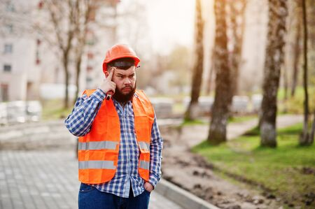 Portrait of brutal beard worker man suit construction worker in safety orange helmet against pavement thinking.