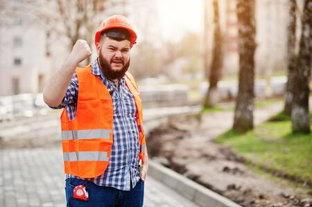 trustworthy: Portrait of brutal angry beard worker man suit construction worker in safety orange helmet against pavement with showing arms. Stock Photo