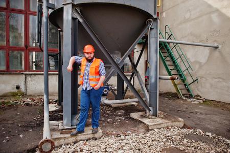 trustworthy: Brutal beard worker man suit construction worker in safety orange helmet stay near big industrial barrel .