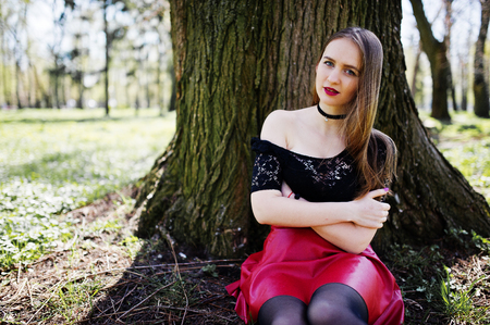 Portrait of girl with bright make up with red lips, black choker necklace on her neck and red leather skirt sitting near tree at park.