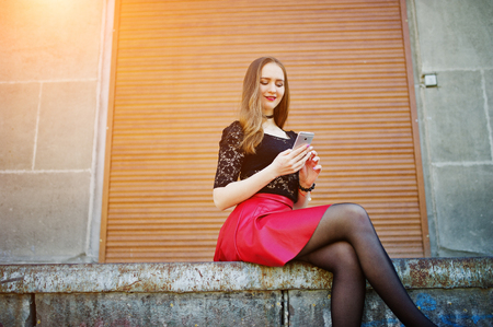 Portrait of girl with black choker on her neck, red leather skirt and mobile phone at hand against orange shutter.