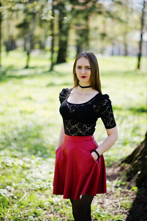 Portrait of girl with bright make up with red lips, black choker necklace on her neck and red leather skirt at spring park. Stock Photo
