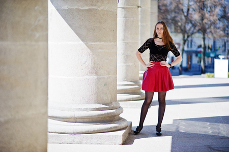 Portrait of girl with black choker necklace on her neck and red leather skirt against stone columns. Stock Photo
