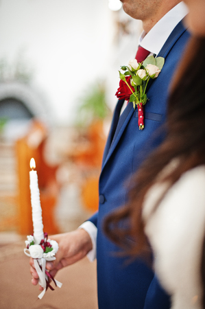 Candle at hand of bride and groom on church wedding.