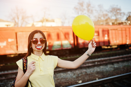 Young teenage girl standing on the platform at the train station with funny lips on stick and balloon at hand, wear on yellow t-shirt, jeans and sunglasses, with backpack. Stock Photo