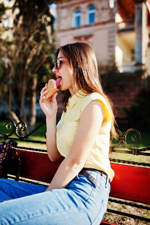 Young teenage girl sitting on bench with ice cream at hands, wear on yellow t-shirt, jeans and sunglasses.